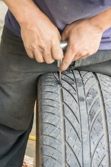 La photo montre que les mécaniciens réparent un pneu qui fuit et un pneu qui scelle
