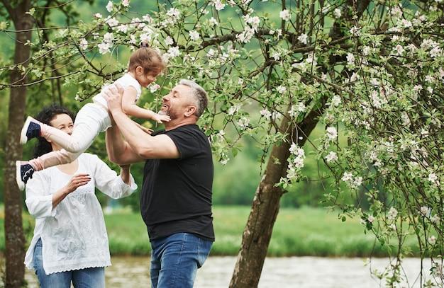 Photo en mouvement. couple gai profitant d'un beau week-end en plein air avec sa petite-fille. beau temps printanier