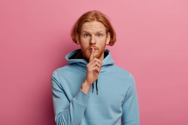 Photo d'un mystérieux homme sérieux avec des cheveux roux et une barbe fait un geste de silence, demande de ne pas dire ses informations secrètes, appuie l'index sur les lèvres, porte un sweat à capuche bleu regarde directement