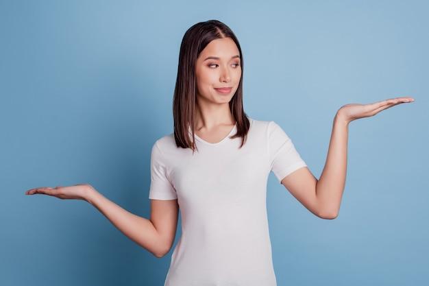 Photo de nice curieuse smart girl palms pesant des objets invisibles espace vide sur fond bleu