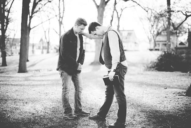 Une photo en niveaux de gris de deux hommes priant ensemble