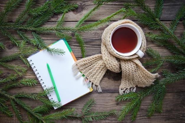 Photo de noël avec une tasse de thé dans une écharpe
