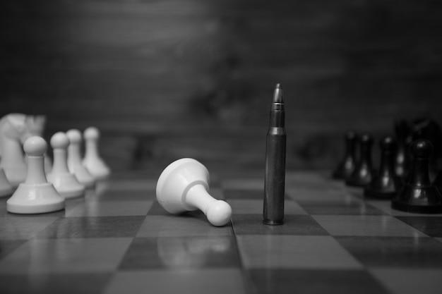 Photo en noir et blanc d'une balle de fusil sur un échiquier. concept de puissance des armes à feu