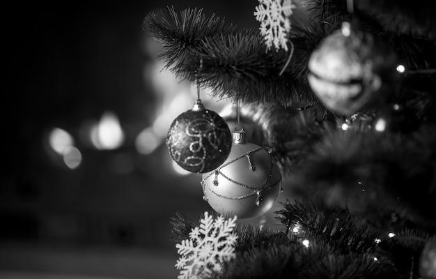 Photo en noir et blanc d'un bel arbre de noël décoré devant une cheminée en feu à la maison. focus sur la cheminée