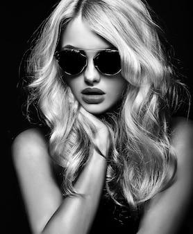 Photo en noir et blanc de belle fille jolie femme blonde à lunettes de soleil