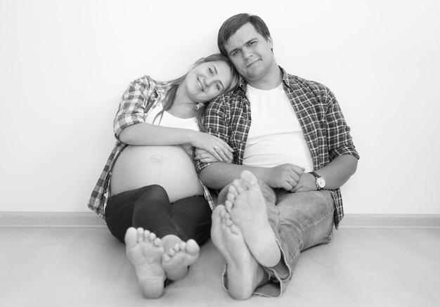 Photo en noir et blanc d'un couple enceinte heureux s'embrassant sur le sol