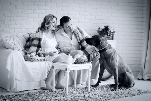 Photo noir et blanc dans un style rétro. famille heureuse assise dans le salon le matin