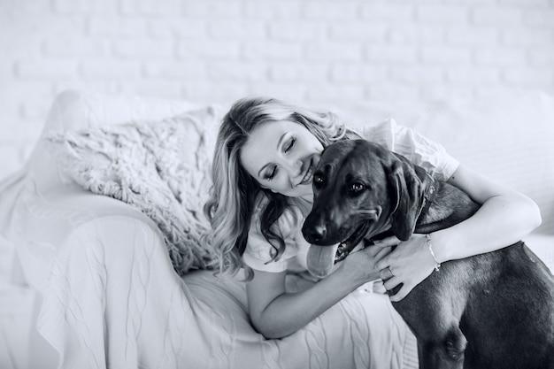 Photo noir et blanc dans un style rétro. portrait d'une jeune femme enceinte avec un chien