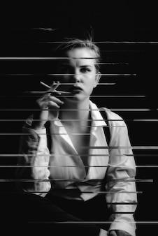 Photo en noir et blanc d'une jeune fille fumant une cigarette