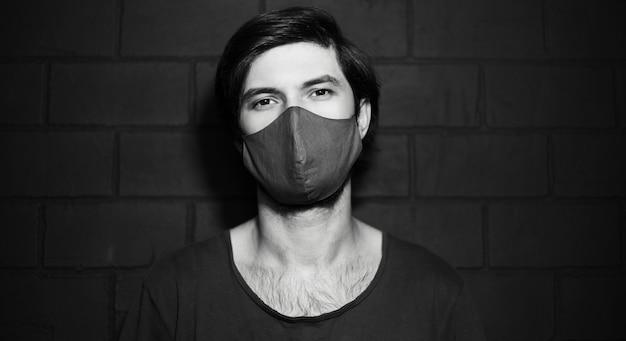 Photo en noir et blanc d'un jeune homme portant un masque médical contre un mur de briques.