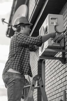 Photo en noir et blanc d'un jeune homme réparant un climatiseur