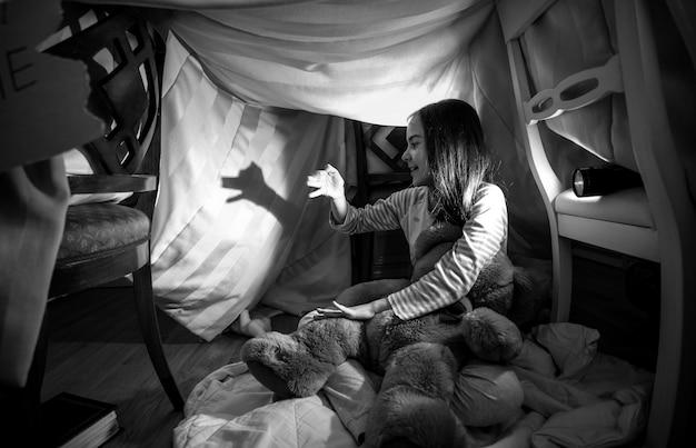 Photo en noir et blanc d'une jolie fille faisant l'ombre d'un chien avec les mains et la lampe de poche