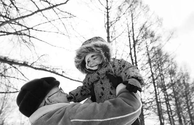 Photo en noir et blanc d'un parent tenant un enfant sur les mains dans un parc d'hiver
