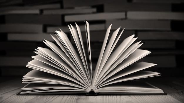 Photo en noir et blanc de vieux livre sur table en bois