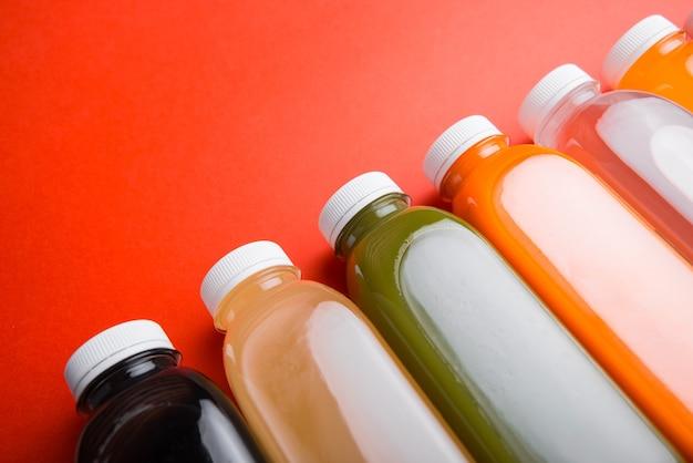 Photo de nombreuses bouteilles de jus de fruits frais de désintoxication sur une surface rouge
