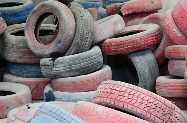 Une photo de nombreux vieux pneus usés laissés dans une décharge