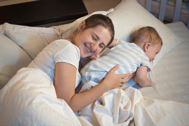 Photo de nuit d'une mère souriante heureuse allongée sur le lit avec son petit bébé