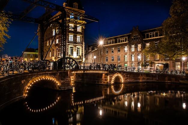 Photo de nuit de la ville, de nombreux vélos sur le pont sur le canal d'amsterdam, pays-bas