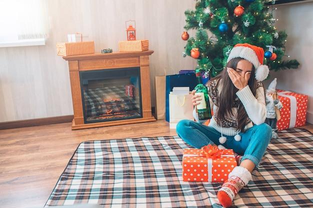 Photo d'oyung womqan est assise sur le sol et tient une bouteille verte avec de l'alcool. elle couvre également le visage avec la main et garde les yeux fermés.