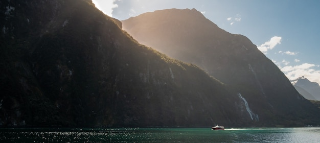 Photo panoramique d'un bateau naviguant dans le fjord par une journée ensoleillée milford soundnew zealand