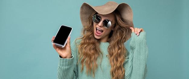 Photo panoramique de la belle jeune femme blonde heureuse portant des lunettes de soleil et un chapeau d'été isolé sur