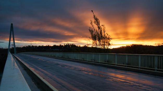 Photo panoramique d'un coucher de soleil depuis un pont avec de beaux rayons rayonnant du soleil