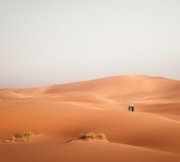 Photo panoramique de deux personnes debout sur un lieu désert