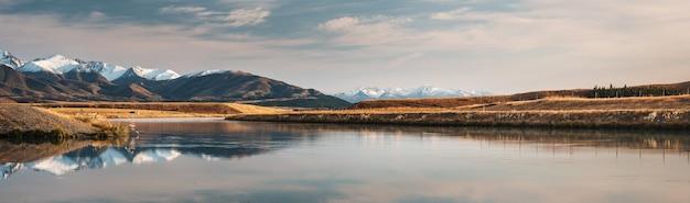 Photo panoramique du canal au-dessous du lac pukaki à twisel entouré de montagnes