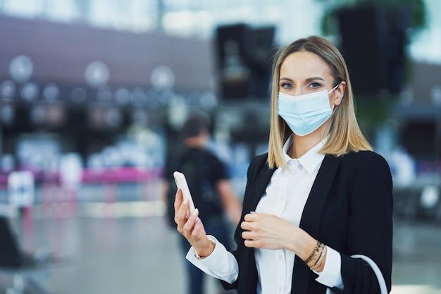 Photo d'une passagère adulte utilisant un smartphone à l'aéroport