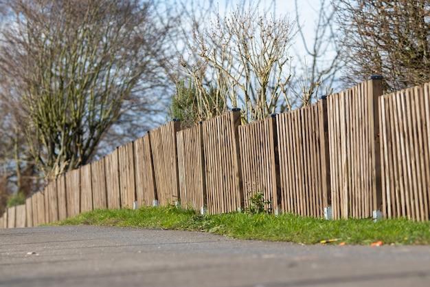 Photo de paysage d'une clôture en bois brun d'une mini forêt avec un ciel bleu clair
