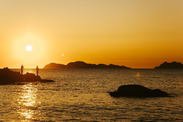 Photo de paysage de deux pêcheurs sous le coucher du soleil