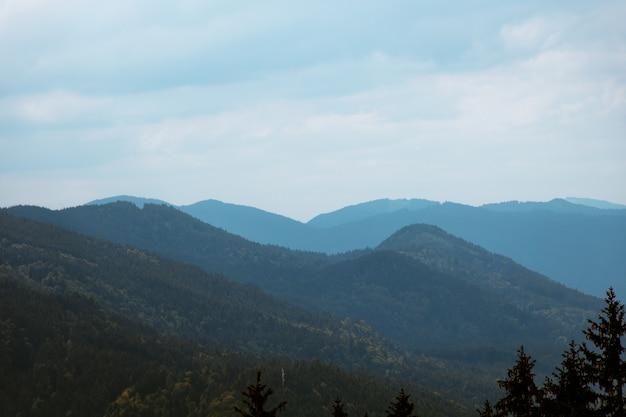 Photo de paysage de montagnes bleues avec un ciel sombre et nuageux