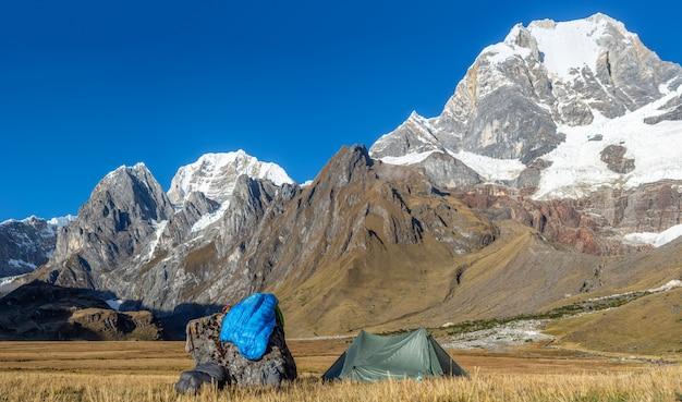 Photo de paysage d'une tente verte près d'un rocher dans un champ entouré de montagnes couvertes de neige