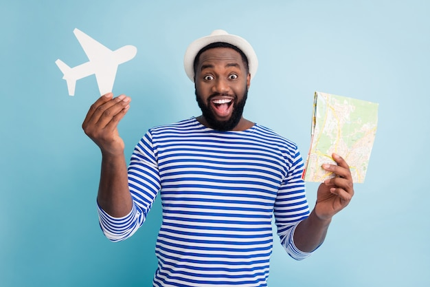 Photo de la peau foncée excitée guy voyageur tenir papier avion carte offre de belles variantes de voyage bon marché bas prix porter bonnet de soleil blanc chemise de marin rayé mur de couleur bleu isolé