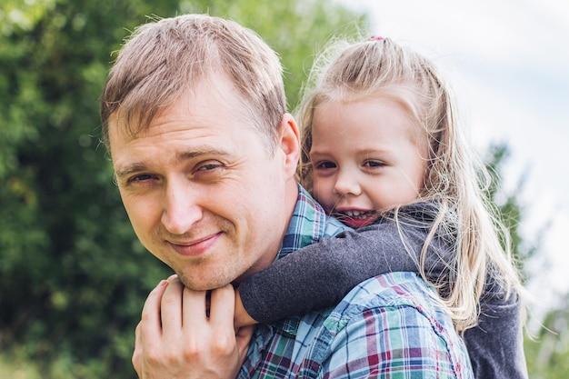 Une photo d'un père et d'une jeune fille jouant sur une pelouse d'été par une chaude journée d'été. fête des pères