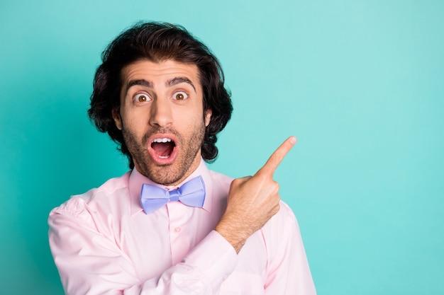 Photo de petit ami drôle mignon surpris porter une tenue rose pointant vers l'espace vide bouche ouverte fond de couleur sarcelle isolé