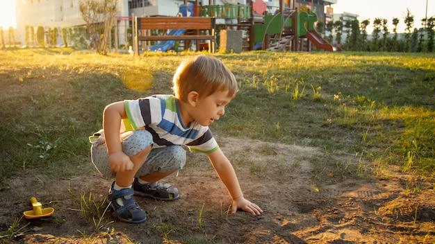 Photo d'un petit garçon de 3 ans assis sur le sol au parc et creusant du sable