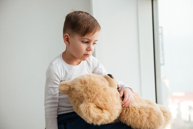 Photo d'un petit garçon triste seul près de la fenêtre avec un ours en peluche attendant les parents à la maison. regarder de côté.