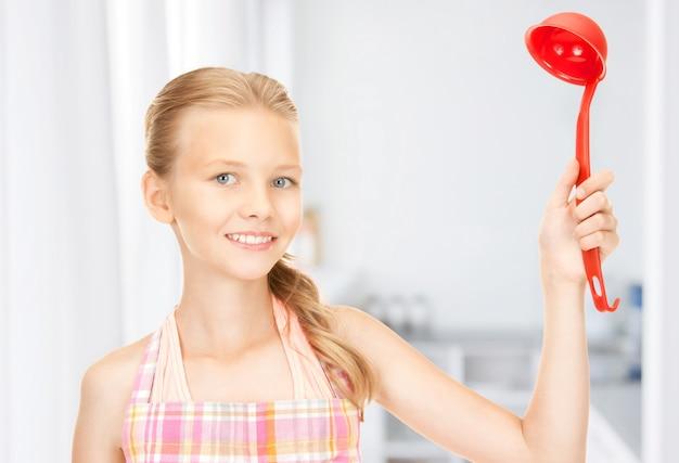 Photo de petite femme au foyer avec louche rouge à la cuisine