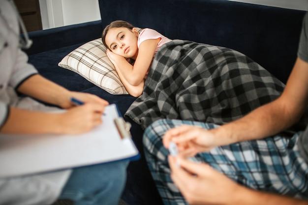 Photo de petite fille allongée sur le canapé. elle a couvert de couverture. femme médecin et père assis à côté de la fille. il tient un thermomètre. docteur écrit prescription de médicaments.
