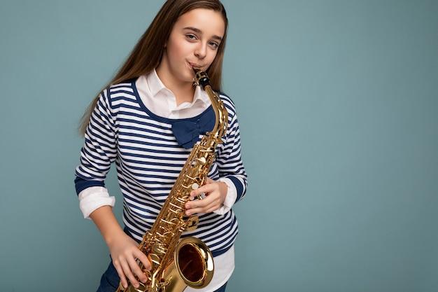 Photo d'une petite fille brune heureuse assez positive portant une chemise à manches longues à rayures élégantes, isolée sur un mur de fond bleu jouant du saxophone en regardant la caméra. espace vide, espace de copie