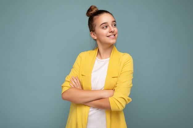 Photo d'une petite fille brune souriante heureuse et positive portant une veste jaune élégante