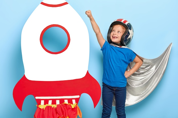 Photo d'une petite fille fait un geste de mouche, prétend avoir un super pouvoir, prêt pour le vol et sauver le monde, porte une cape