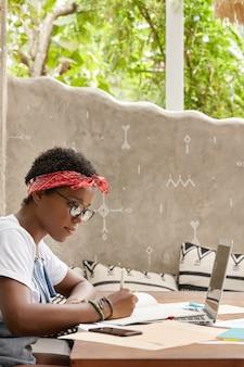 Photo d'un pigiste concentré prépare le calendrier de la journée de travail, écrit dans les documents