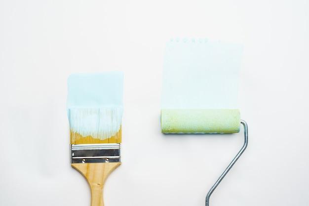 Photo de pinceau et rouleau avec de la peinture bleue sur fond blanc vierge