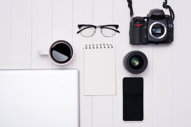 Photo à plat du bureau de l'espace de travail avec ordinateur portable, smartphone, café, lunettes et appareil photo reflex numérique