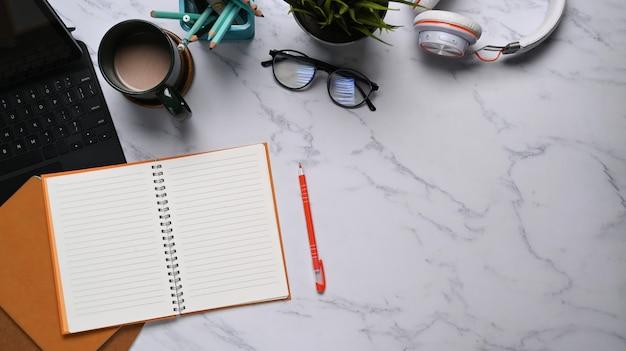 Photo à plat de l'espace de travail avec un cahier vide, une tablette, des lunettes, un casque et une tasse à café sur fond de texture de marbre. espace de copie.