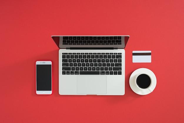 Photo à plat de l'espace de travail avec ordinateur portable moderne, smartphone, café et carte de crédit, sur fond de couleur.