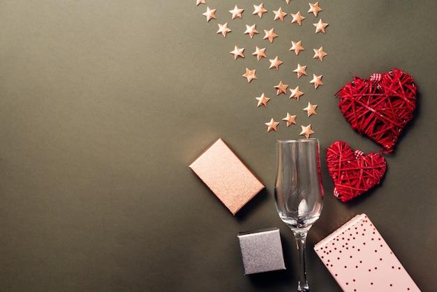 Photo à plat d'étoiles avec verre de champagne et coffrets cadeaux avec des coeurs rouges, des cadeaux pour la saint valentin ou un anniversaire