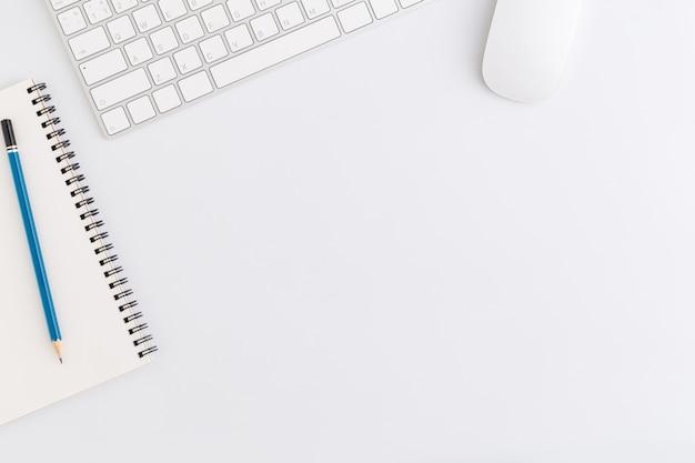 Photo plate de bureau avec souris et clavier, espace copie sur fond blanc, vue de dessus